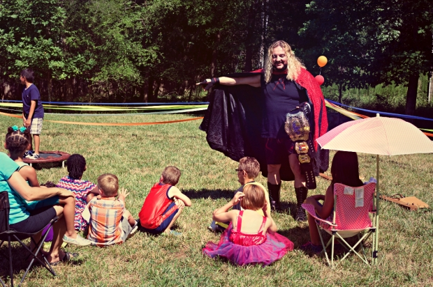 Rob Kellum (Angus) entertains some children and their parents during a circus party scene.